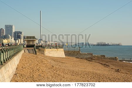 Shingle beach and seafront promenade with i360 observation tower and piers in background. East Sussex England. With unrecognizable people.