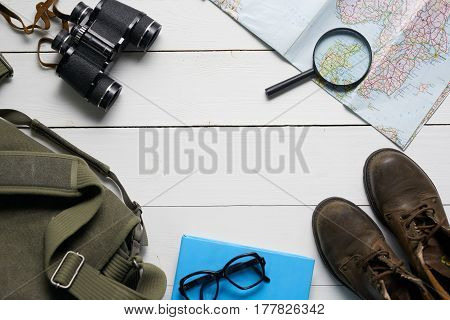 Top view flat lay of a travel set consisting of bag, binoculars, old hiking boots, map and magnifying glass, over white wooden planks