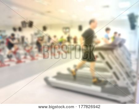 Abstract Blurred Image Background Of People And Exercise Equipments In Modern Fitness Gym.