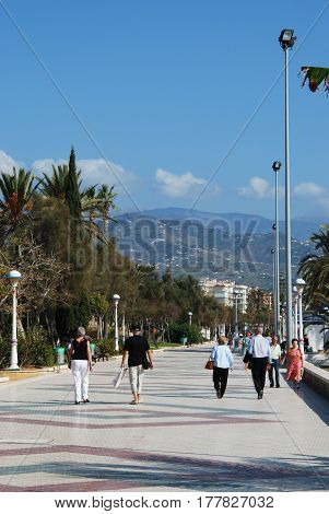 TORRE DEL MAR, SPAIN - OCTOBER 27, 2008 - View along the promenade towards the mountains with tourists enjoying the setting Torre del Mar Malaga Province Andalusia Spain Western Europe, October 27, 2008.