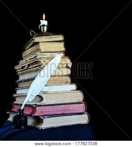 High stack of old books a burning candle in a candlestick and a white feather in the inkwell