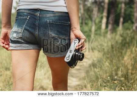 Female journalist with camera walking on forest trail, working outdoors. Profession and occupation concept.