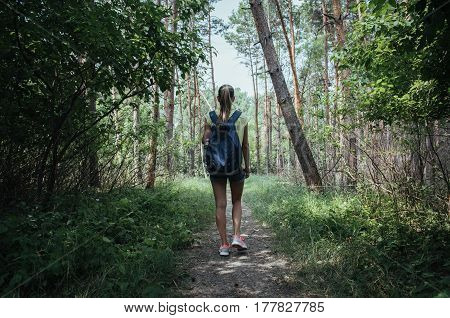Active female hiker with backpack trekking through natural park in summer. Concept of camping, vacation and tourism.