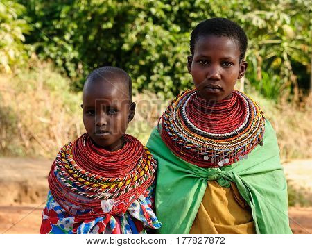 SOUTH HORR KENYA - JULY 08: Young African girls from the Samburu tribe with characteristic decorative necklaces on the market in Kenya South Horr in July 08 2013