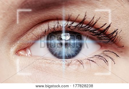 Macro shot of human blue eye with laser rays . Concept of eyesight verification, diagnosis, disease and clinical treatment.
