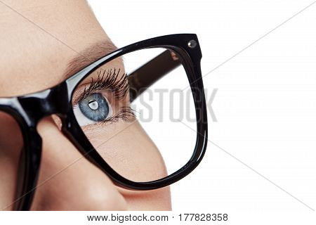 Close-up of female with blue eyes wearing spectacles over white background with space for text. Concept of vision correction and eye care.
