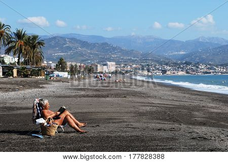 TORRE DEL MAR, SPAIN - OCTOBER 27, 2008 - Woman sunbathing on the beach reading a book with views towards the mountains Torre del Mar Malaga Province Andalusia Spain Western Europe, October 27, 2008.