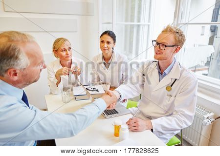 Doctor gives handshake to senior patient during consultation