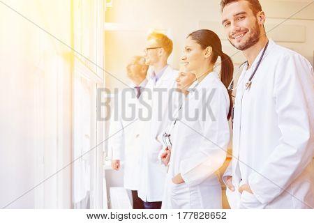 Team of doctors looking at window in hospital as group