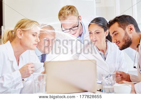 Team of doctors working with computer with light beam in hospital