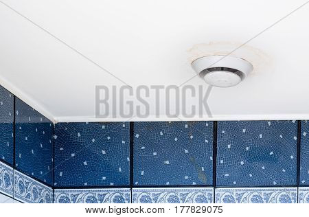 Round air ventilation frame on white ceiling with wet stains streaks and mould around ventilator.