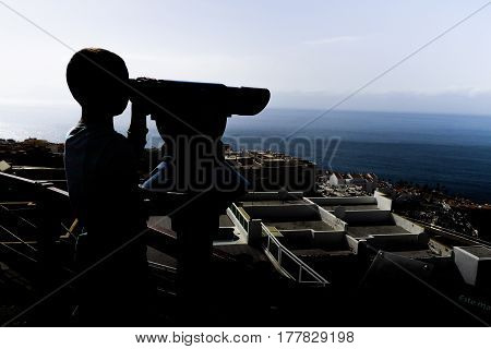 Young boy is looking through binoculars. Sightseeing point. Beautiful views of the city and ocean in the background.