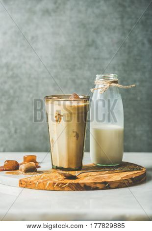 Iced caramel latte summer coffee cocktail with milk and frozen coffee ice cubes in glass on serving olive wood and marble board over grey table, dark plywood wall, selective focus, copy space