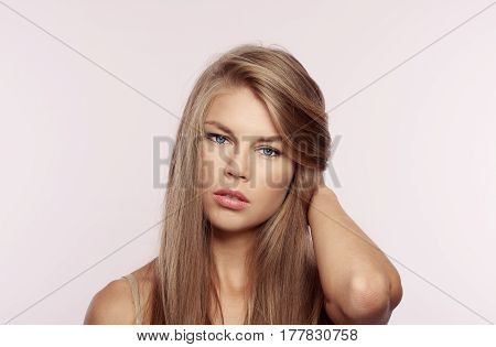 Portrait of gorgeous woman with flawless skin and shiny hair posing on pink background in studio. Concept of face hydration, treatment and moistening.