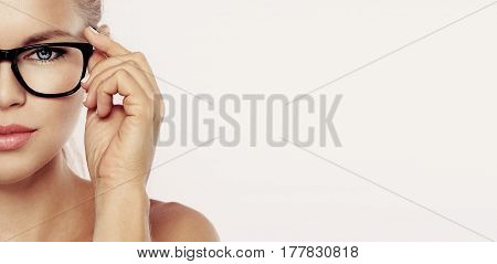 Closeup portrait of young beautiful woman face in spectacles over pink background with copy space. Concept of vision, eye care and medicine.