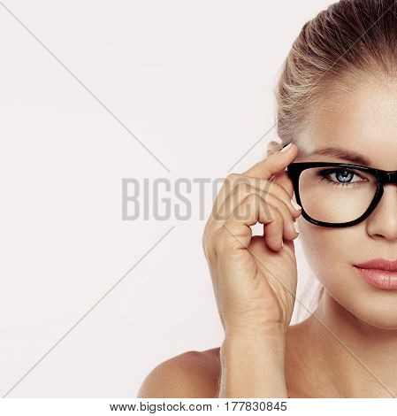 Close up of attractive female face putting on optical eyeglasses. Concept of ophthalmologic clinic, eyes examination and treatment.