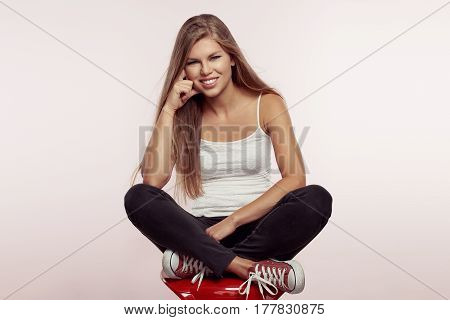Studio portrait of young trendy female model wearing street casual clothing and shoes. Fashion girl sitting on red chair with crossed legs.