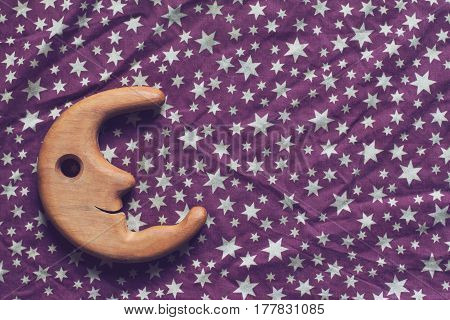 top view concept wrinkled background texture of purple textile table cloth with white stars and wooden toy moon smiling on the left