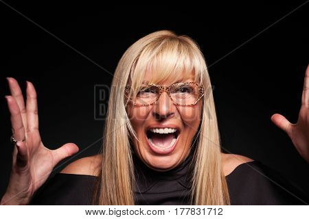 Mature woman with glasses screaming hysterically in rage
