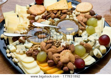 Cheese plate served with nuts, grapes, honey and crackers