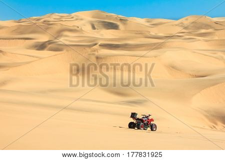 Quad driving in sand desert. ATV in the middle of nowhere. Africa.