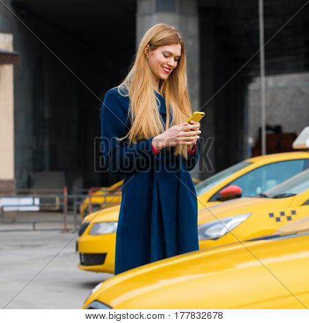 A young girl calls a taxi by phone. Happy blonde woman on smart phone walking in blue coat.