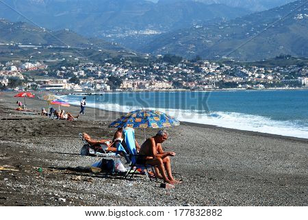 TORRE DEL MAR, SPAIN - OCTOBER 27, 2008 - Tourists relaxing on the beach with views towards the mountains Torre del Mar Malaga Province Andalusia Spain Western Europe, October 27, 2008.