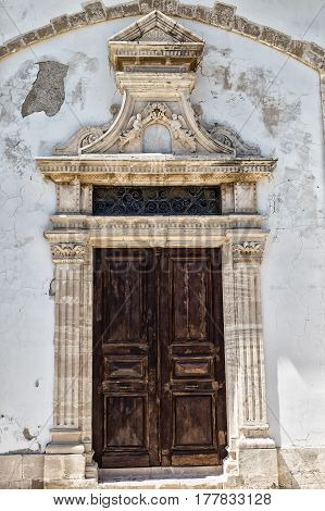 Ancient wooden carved door with stucco molding on the facade of the white building