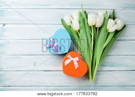 White tulips bouquet and heart shaped gift boxes on wooden background. Top view with space for your greetings