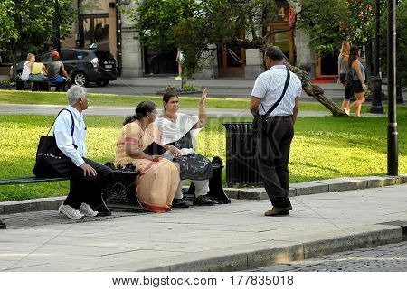 Oslo Norway - July 22 2014: group of hindu tourist talking and laughing on bench in the park Eidsvolls Plass