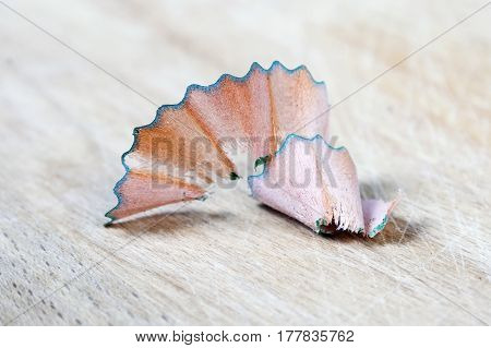 Pencil shaving is isolated on a wooden background