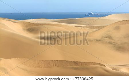 Sand dune desert meets water of the Atlantic Ozean. Ships and boats on the water.