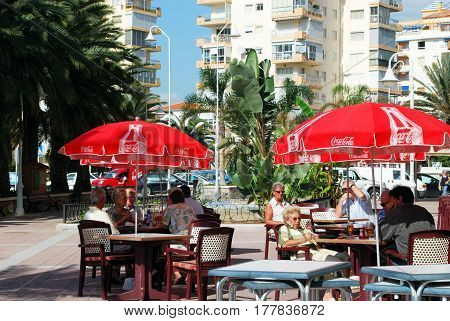 LAGOS, SPAIN - OCTOBER 27, 2008 - Tourists relaxing at a pavement cafe with red parasols Lagos Malaga Province Andalusia Spain Western Europe, October 27, 2008.
