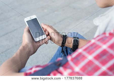 Man in casual clothing feels comfortable sitting on the stairs holding hands and talking phone on the Internet.