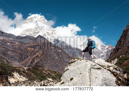 Sportive Man with Backpack and walking Poles staying on grey Rock and looking on Mountain Landscape high snowy Peak and blue Sky on Background
