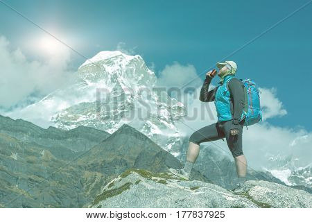 Male Hiker drinking Refreshment staying on top of Rock and enjoying Mountain View of high altitude Himalaya Summit soft toned with copy space