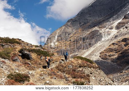 Group of People of different age and ethnicity walking up on Mountain Trail towards Pass throw the Cliff during Hike in Nepalese Himalaya