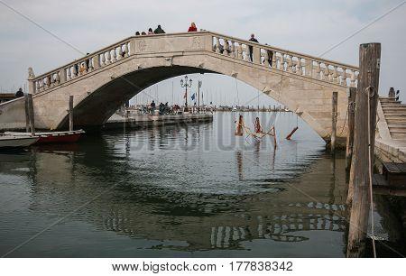 CHIOGGIA, ITALY - MARCH 19, 2017: Tourist in the historic bridge of Chioggia, Veneto.