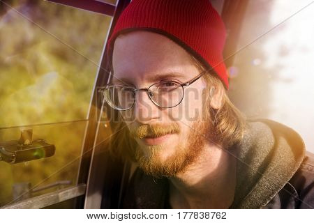 portrait of handsome bearded red-haired man sitting in a cableway