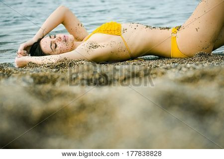 Pretty girl or beautiful woman sexy brunette dirty with natural sand in yellow swimsuit sleeping on sea beach with transparent water outdoors on sunny summer day on grey sandy background