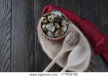 Quail eggs in red pot and kitchen tools. Healthy  food concept on wooden table