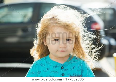 Cute baby boy with long blond hair walking on city street on sunny summer day outdoors on blurred background
