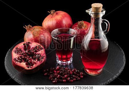 Pomegranates, seeds and juice on black plate with black background