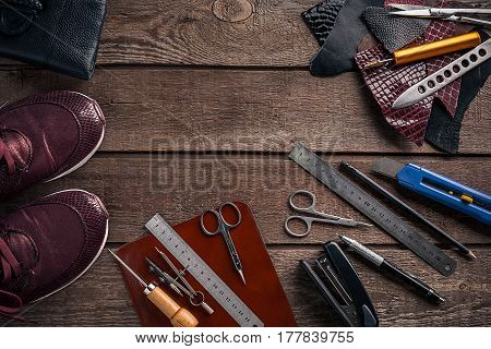 Leather craft or leather working. Leather working tools and cut out pieces of leather on work desk. Still life. Copy space. Top view