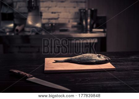 Fresh fish on a wooden cutting boarditchen bayleaf. Photo in brown tones. Kitchen. Wooden table