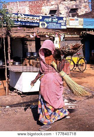 JAIPURA, INDIA - NOVEMBER 22, 1993 - Indian woman walking along a village shopping street carrying a basket Jaipura Rajasthan India, November 22, 1993.
