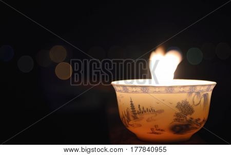 Candle in the dark background of space and lights. Fire inte a bowl for the Chinece ceremony