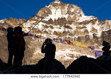 Silhouettes of Mountain Climbers pointing by walking Sticks to the Direction of high Peak illuminated by Evening Sunlight and traditional Buddhist Prayer Flags in Nepal