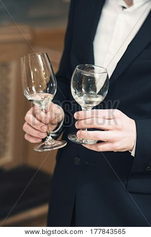 a lot of different wine glasses on the table at wine tasting. sommelier at wine tasting talks about how different forms of glasses affect on the taste of a wine