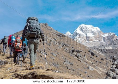 Group of Mountain Climbers walking up on yellow steep Footpath carrying large expedition Backpacks
